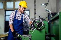 Drejarearbetaren arbetar p? en drejb?nkmaskin i en fabrik royaltyfria bilder
