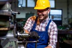 Drejarearbetaren arbetar p? en drejb?nkmaskin i en fabrik royaltyfri bild