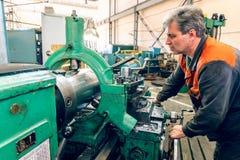 Drejarearbetaren klarar av den metalworking processen av mekaniskt klipp på en drejbänk arkivbilder