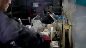 Drejaren arbetar med den roterande maskinen i ett seminarium av industrianläggningen som bearbetar metalldetaljen lager videofilmer