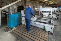 Drejaren fungerar på en mekanisk drejbänk Vändande arbeten, metall som bearbetar, genom att klippa Royaltyfri Bild