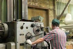 Drejaren fungerar på en mekanisk drejbänk Vändande arbeten, metall som bearbetar, genom att klippa Royaltyfri Foto