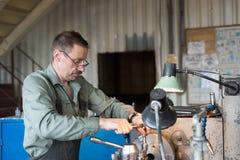 Drejaren fungerar på en mekanisk drejbänk Vändande arbeten, metall som bearbetar, genom att klippa Arkivfoton
