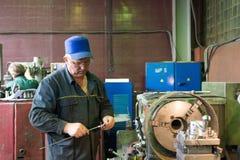 Drejaren fungerar på en mekanisk drejbänk Vändande arbeten, metall som bearbetar, genom att klippa Arkivbilder