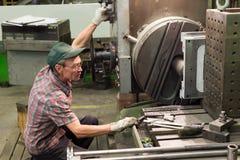 Drejaren fungerar på en mekanisk drejbänk Vändande arbeten, metall som bearbetar, genom att klippa Arkivbild
