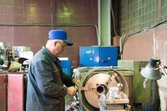 Drejaren fungerar på en mekanisk drejbänk Vändande arbeten, metall som bearbetar, genom att klippa Royaltyfri Fotografi