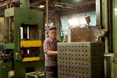 Drejaren fungerar på en mekanisk tråkig maskin Vändande arbeten, metall som bearbetar, genom att klippa Arkivfoto