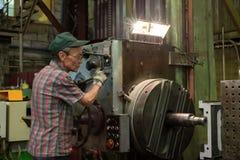 Drejaren fungerar på en mekanisk tråkig maskin Vändande arbeten, metall som bearbetar, genom att klippa Arkivbild