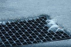 Dren de la tormenta del agua de la calle con la salida que fluye pesada Imagen de archivo libre de regalías