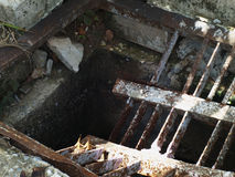 Dren quebrado, viejo, y oxidado del lado del camino Foto de archivo