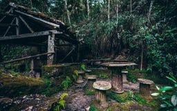Drenaje-bien abandonado oscuro en selva tropical con la tabla y los taburetes cerca Fotografía de archivo