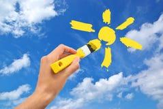 Drenaje de la mano el sol en cielo Fotos de archivo