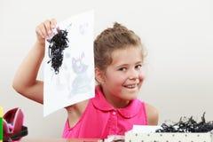 Drenaje de la niña en la sala de clase Fotos de archivo