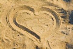 Drenaje del corazón en la arena Foto de archivo libre de regalías