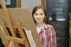Drenaje joven sonriente de la muchacha del artista Imagenes de archivo