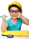 Drenaje lindo de la niña con la etiqueta de plástico que desgasta el sombrero duro Foto de archivo