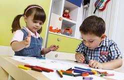 Drenaje preescolar de dos niños con los creyones Imagen de archivo