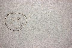 Drenaje sonriente de la cara en arena imágenes de archivo libres de regalías