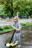 Drenched in the rain, a boy in a sport suit skates on a scooter. Spring walk in the city park, rainy weather. Royalty Free Stock Photography