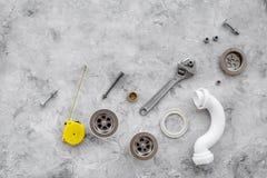 Drene partes e ferramentas do encanamento no copyspace de pedra cinzento da opinião superior do fundo imagem de stock