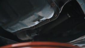 Drenuje starego olej od silnika przez rynsztokowej prymki Strumień, barłóg zdjęcie stock