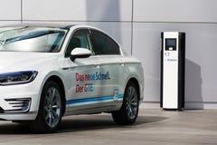 Plug-in hybrid electric car Volkswagen Golf GTE stands by charging station in front of the Glaserne Manufaktur. DRESDEN, GERMANY - APRIL 2 2018: Plug-in hybrid Royalty Free Stock Images