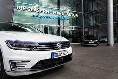 Plug-in hybrid Volkswagen Golf GTE and e-Golf electric cars stand by charging station in front of the Glaserne Manufaktur. DRESDEN, GERMANY - APRIL 2 2018: Plug Stock Photo