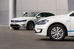 Plug-in hybrid Volkswagen Golf GTE and e-Golf electric cars stand by charging station in front of the Glaserne Manufaktur