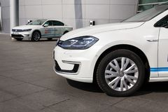 Plug-in hybrid Volkswagen Golf GTE and e-Golf electric cars stand by charging station in front of the Glaserne Manufaktur. DRESDEN, GERMANY - APRIL 2 2018: Plug Stock Photography