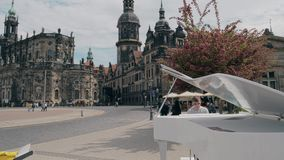 DRESDEN, GERMANY - MAY 2, 2018. Young man playing piano in the centre of the city. DRESDEN, GERMANY - MAY 2, 2018. Young man playing the grand piano Royalty Free Stock Photography