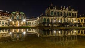 Dresden vid natt, den Tyskland slotten Zwinger reflekterade vatten Arkivbild