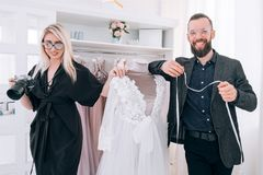 Dress boutique personal assistant photographer. Luxury dress boutique. Modern business and cooperation. Personal assistant and photographer presenting gowns stock photography
