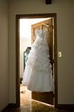 Dress of the bride. Hanging on a hanger on an open door Royalty Free Stock Photo