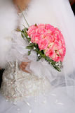 Dress of the bride. The bride in a wedding dress with a bouquet from roses Royalty Free Stock Photos