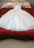 Dress of the bride on a bed. Bride dress lays on a red bed Stock Images