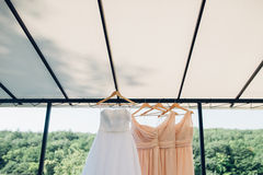 Dress for the bride and her bridesmaids hanging on hangers Stock Image