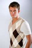 Dress casual look. Young man poses wearing argyle sweater Royalty Free Stock Photos