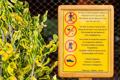 Dress code restricting sign at a restaurant next to a pool and beach (horizontal) Royalty Free Stock Photos