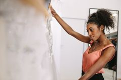Woman entrepreneur in her fashion boutique. Dress designer in her cloth shop with designer clothes on display. Customer observing design on dress in a fashion Stock Images