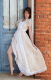 Dress in Doorway. An image of a pretty woman in a vintage dress in a blue doorway royalty free stock image