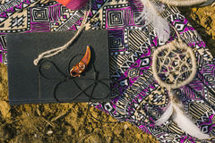 Dress, dreamcatcher and book lying on dry land. hipster style Royalty Free Stock Image