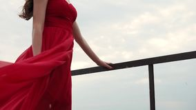 Dress fluttering under the gusts of air, a lady staring to distance on the sea. The woman in the scarlet dress is standing on the street, her evening dress is stock video footage