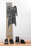 Dress hanging on a mirror, and row of shoes Royalty Free Stock Images