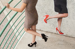 Dress, Legs, and Heels. An image of an anonymous young woman in heels lifting her leg in front of  similar image on the wall behind her Royalty Free Stock Photo