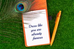 Dress like you are already famous. Text in notebook with peacock feather , pen and heart shape on grass stock image