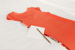 Dress with a pencil and paper on bed Royalty Free Stock Image