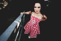 Dress in red polka dot. Beautiful bright young girl in a red dress with polka dots against a dark underground passage Royalty Free Stock Image