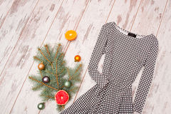 Dress in rhombuses on a wooden background, fur-tree branch with ornaments and citrus Royalty Free Stock Photo