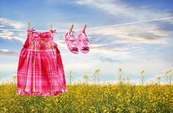 Dress and sandals on clothesline in summer Stock Photo