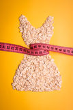 Dress shape made from oatmeal with measuring tape Royalty Free Stock Photos